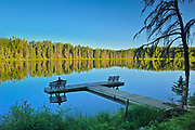 Tourist sitting on a bench on a dock,  admiring the view of a northern lake<br /><br />Manitoba<br />Canada
