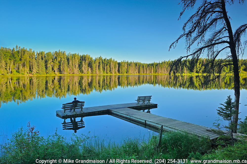 Tourist sitting on a bench on a dock,  admiring the view of a northern lake<br />
