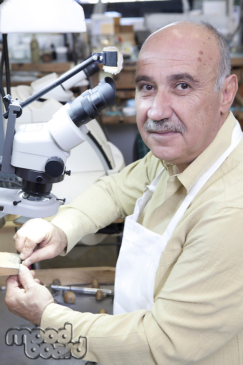 Portrait of skilled mature man with microscope in jewelry repair shop