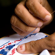 Women working on sewing typical Panamanian dresses in the town of Rincon Santo in the region of Ocu, Province of Herrera, Republic of Panama.  Ocu is an area of the country well known for the fabrication of typical Panamanian dress.