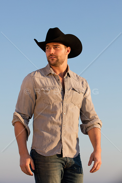 cowboy outdoors in a denim shirt against a blue sky