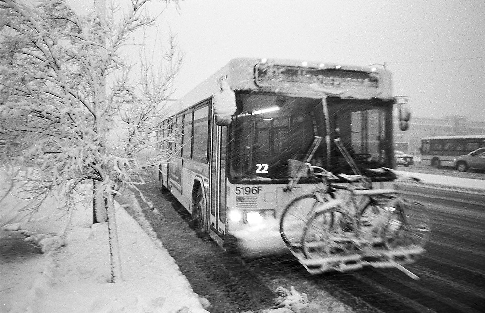 A city bus carrying bikes drives past in a snow storm in Boulder, Colorado.