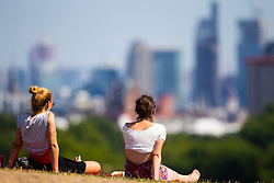 Friends Paulina Michor, 21, left and Alex Szyszko, 23 a view of the capital's skyline in the hot sunshine on Primrose hill in North London. London, August 06 2018.