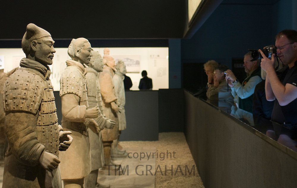 Tourists photograph Terracotta warriors on display in the Shaanxi History Museum, Xian, China