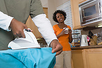 Mid-adult man ironing shirt, his girlfriend looking at him, in domestic kitchen