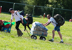 © Licensed to London News Pictures. 24/06/2015. Pilton, UK.   Festival goers at Glastonbury Festival pull a trolley stacked with beer up a steep hill as they rush to find the best area to set up their tents shortly after entering the site at 8am on  Wednesday Day 1 of the festival.        The pedestrian gates to the festival opened at 8am this morning, with many festival goers arriving and waiting throughout last night for the opening.  This years headline acts include Kanye West, The Who and Florence and the Machine, the latter having been upgraded in the bill to replace original headline act Foo Fighters.  Photo credit: Richard Isaac/LNP