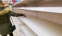 © Licensed to London News Pictures. 03/03/2018. Salford, UK. A shopper runs her hand along empty shelves, depleted of all stock of bread, at a branch of Sainsbury's supermarket in Salford today as it's reported snow has prompted panic buying of food staples . Photo credit: Joel Goodman/LNP