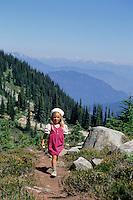 Girl, 4-5, hikes a trail on Whistler Mountain, walking towards the camera, Whistler, BC Canada.