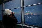 Fotografieren im Winter: die sonnigen Berggipfel der Freiburger Voralpen gesehen durch das vereiste Fenster der Luftseilbahn Moléson. Vu des préalpes fribourgeoises ensoleillés à travers la vitre gelée du télécabine du Moléson