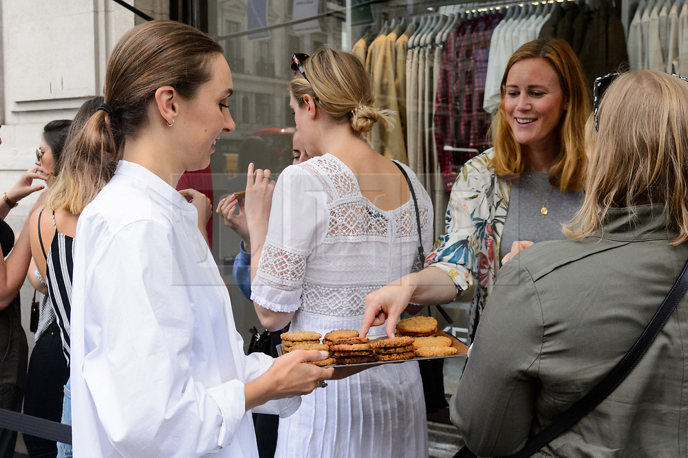 © Licensed to London News Pictures. 25/08/2017. London, UK. Member of staff hands out cookies to queuing customers at the opening of H&M group's first ARKET flagship store in Regent Street is situated next to Weekend store and a H&M store. ARKET has called itself a modern day market seeing not only clothes, but homeware as well as a small cafe space. Photo credit: Ray Tang/LNP