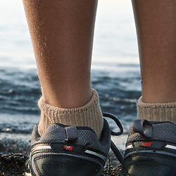 Boy wears Nike sports shoes at beach.