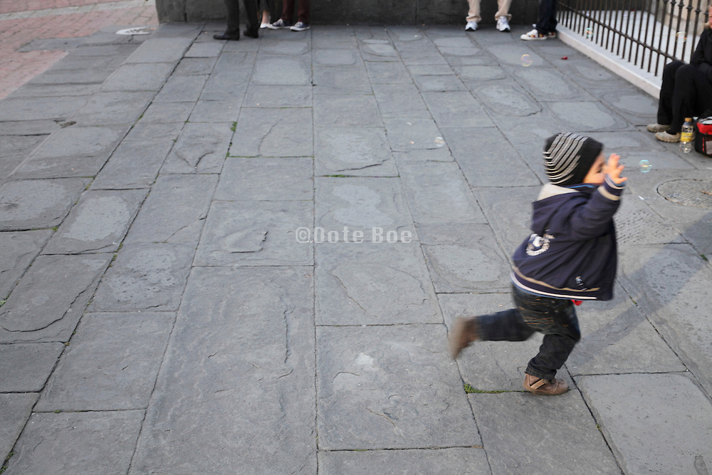 little child trying to catch soap bubbles
