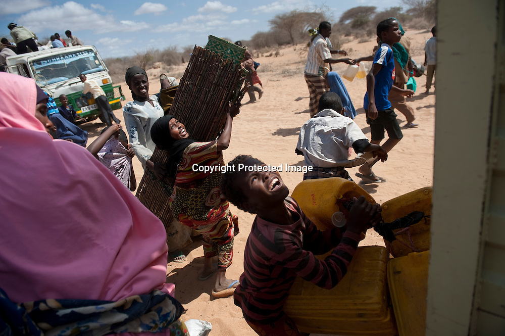 Refugees hurry to place their belongings on trucks to take them to be resettled from the outskirts of the camps to more established dwellings at Kenya's Dadaab Refugee Camp, situated northeast of the capital Nairobi near the Somali border.