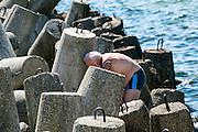 Hel (woj. pomorskie) 20.07.2016. Mężczyzna z telefonem, falochron na Helu<br /> .