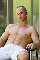 man without a shirt sitting outdoors at home