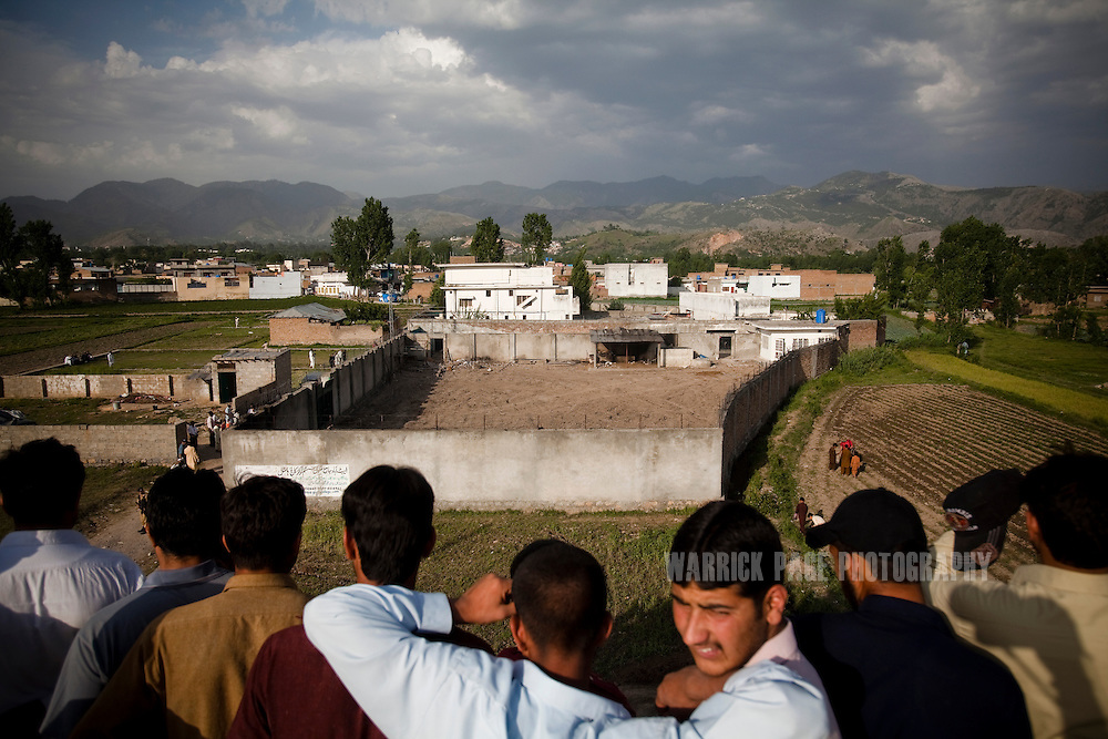 Locals look from atop an adjacent building to the compound where Osama Bin Laden was killed in an operation by US Navy Seals, on May 4, 2011, in Abottabad, Pakistan.  The operation, code-named Operation Neptune Spear, was launched from neighbouring Afghanistan by Seal Team Six. U.S. forces took bin Laden's body to Afghanistan for identification, then dumped it the Arabian Sea. Pakistan has since been widely suspected as having prior knowledge of his whereabouts as the compound was less than a kilometre from the country's biggest military academy. Osama bin Laden was allegedly responsible for supporting the bombing of the US Embassy in Nairobi, Kenya, the attack on the USS Cole and the suicidal attacks of September 11, 2001 in the US. (Photo by Warrick Page)