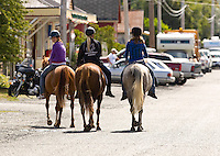 Riding horseback, three young girls go for a stroll down the main street of the small community of Sointula on Malcolm Island.  Sointula, Malcolm Island, Northern Gulf Islands, British Columbia, Canada.