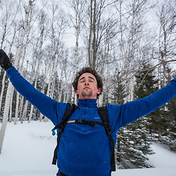 A man stretches after running in New Hampshire's White Mountains on a snowy winter day.
