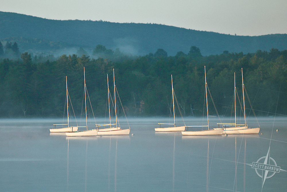 Sailboats at mooring on foggy lake.