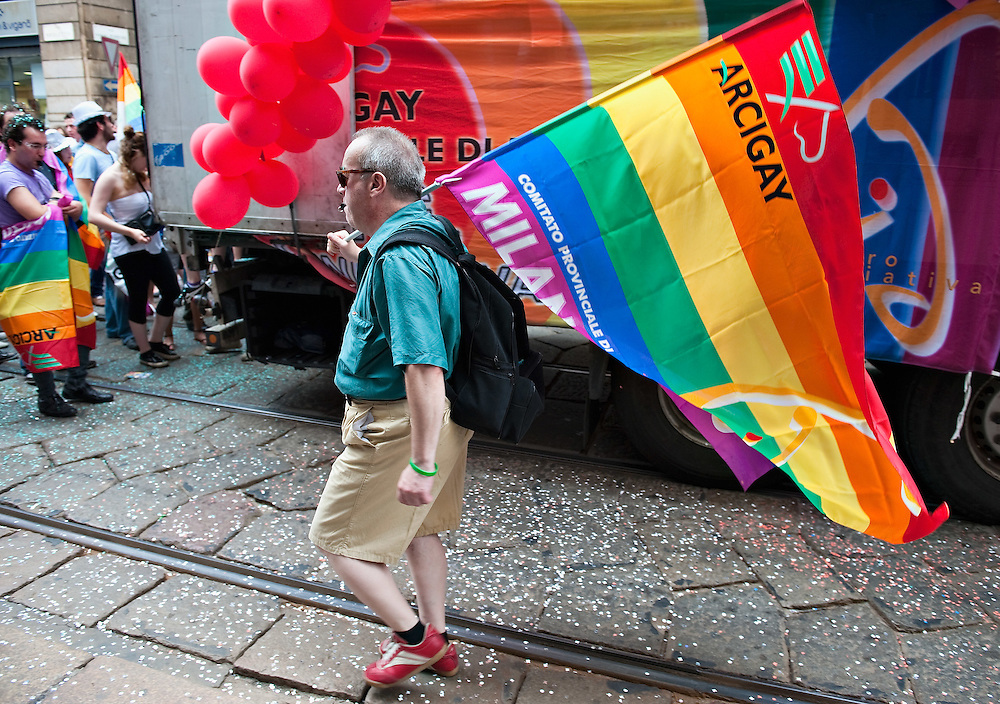 MILAN, ITALY - JUNE 12:  One of the participants to the Gay Pride Milano walks with an ArciGay Milano flag during the march on June 12, 2010 in Milan, Italy.  Pride Milano is one of the oldest gay marches in Italy and today's march is against homophobic violence  (Photo by Marco Secchi/Getty Images)