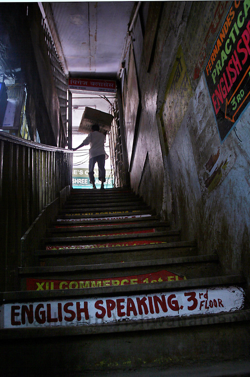 A labourer walks inside a building housing many of the English Speaking Classes adjacent to the Dadar station, in Mumbai, India, on Monday August 20, 2007. Photographer:  Prashanth Vishwanathan