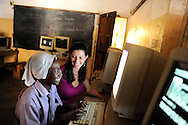 Gabrille Fondiller, founder of Hatua Likoni foundation talks to one of the foundation's scholarship students during a computer class at  Likoni Hill Academy..