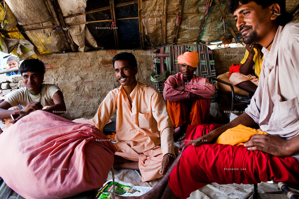 "A group of travelling Rajasthani snake charmers sit in their temporary camp in remote Lodha Basti, Manana village, Samalkha town, Haryana, India on 15th June 2012. ""The government banned our trade but didn't give us any alternative options of livelihood,"" says Baba Prakash Nath (extreme right), a snake charmer. India's traditional snake charmer communities suffer from a loss of livelihood because of stringent wildlife laws and  are forced to resort to begging or working as daily wage labourers. A new program to encourage the snake charmer's children to attend school is underway, to keep them from becoming daily-wage child labourers or joining their parents in scavenging and begging in cities. Photo by Suzanne Lee for The National"