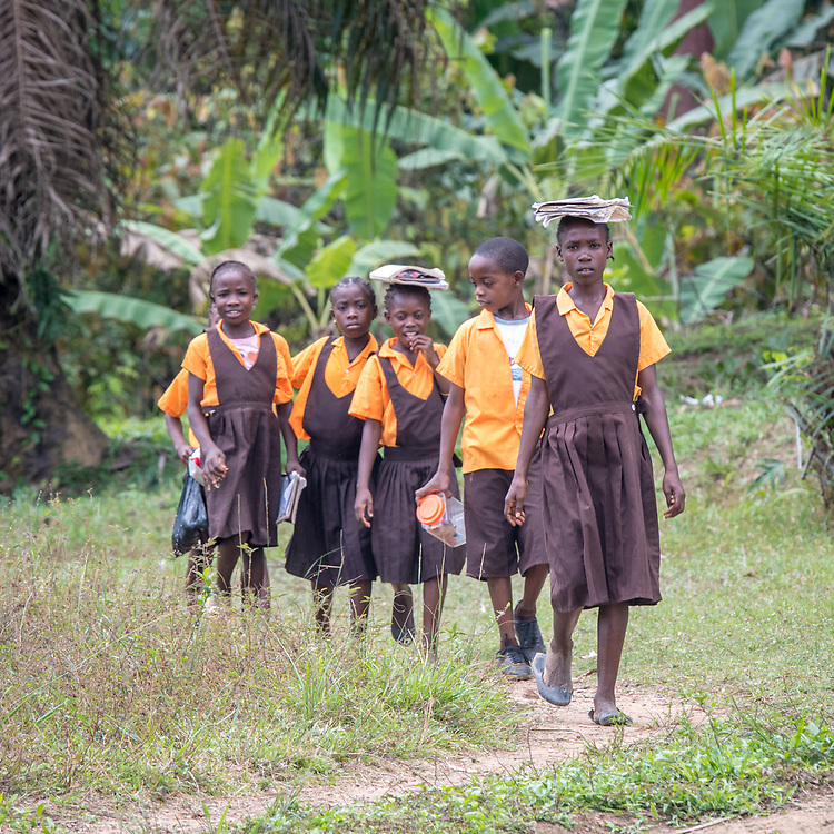 A group of school children walk along a path in Ganta, Liberia