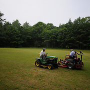 7/3/11 -- Rt 129 , Maine. Jim and Nancy Bailey chat for a bit while finishing up the grass for the day. ..A stretch of the road not often traveled. Spanning communities, classes and styles ~ of farmers and fishermen, retired and plugging, the elite and working waterfront. (This area has huge potential for great photojournalism).  Photo by Roger S. Duncan.