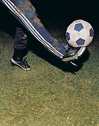 A football is balanced on the boot of a player.