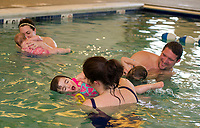 """Through song and play Brooke with her mother Raechel Moulton practice """"windshield wipers"""" during the Taylor Home's Water Babies/Grandbabies class on Saturday morning.  (Karen Bobotas/for the Laconia Daily Sun)"""