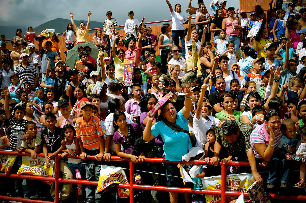 Families cheer as volunteers for the Johan Santana Foundation pass out toys during an annual charity event in Tovar, Venezuela.