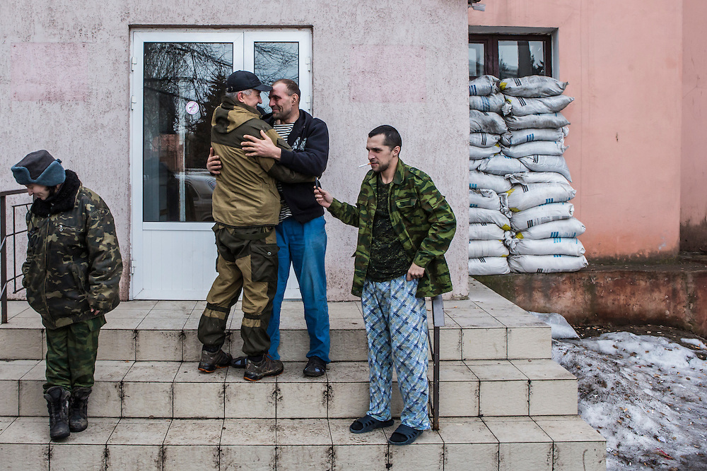 GORLOVKA, UKRAINE - JANUARY 31, 2015: Batya, a rebel commander second from left, greets a wounded comrade outside a hospital in Gorlovka, Ukraine. Fighting in Ukraine has intensified over the last week, with rebels declaring the end of a September ceasefire. CREDIT: Brendan Hoffman for The New York Times