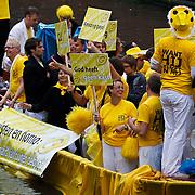NLD/Amsterdam/20100807 - Boten tijdens de Canal Parade 2010 door de Amsterdamse grachten. De jaarlijkse boottocht sluit traditiegetrouw de Gay Pride af. Thema van de botenparade was dit jaar Celebrate, Christenboot, homo met bord Happy Gay