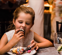 little girl at a wedding eating dessert