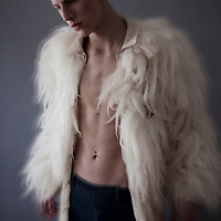 blonde boy with piercings looking away from the camera. He is wearing a furry jacket, with his chest visible.