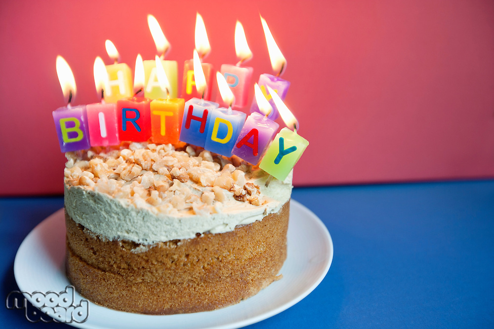 Close-up of candles burning on birthday cake over colored background