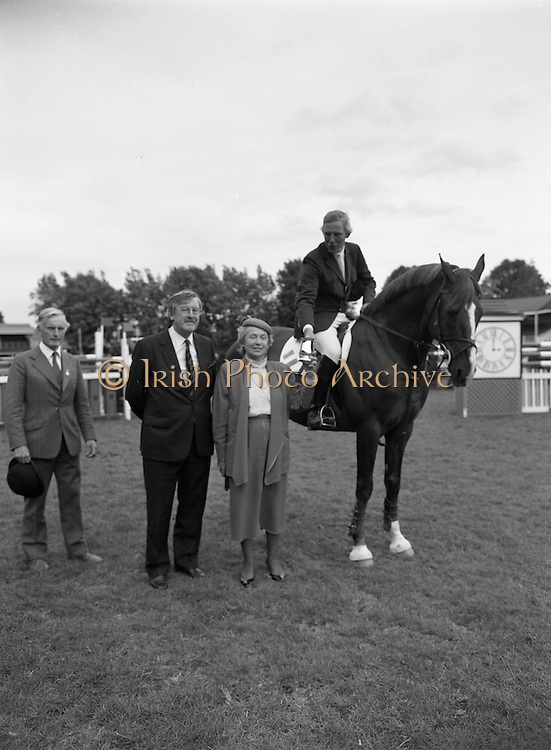 """08/08/1987<br /> 08/08/1987<br /> 08 August 1987<br /> RDS Horse Show, Ballsbridge, Dublin. The Guinness Championship Tankards. Sylvia Bodell, wife of Ernest Bodell (2nd left) Director of Guinness Ireland, presenting the Guinness Championship Gold Tankard for the leading international rider of the Dublin Horse Show 1987, to Eddie Macken (Ireland) on """"Carroll's Flight"""". Also in the picture is Colonel Billy Ringrose, Chairman, Equestrian Committee, RDS."""