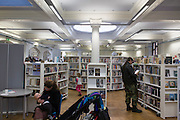 A breastfeeding mother in Carnegie Library, Herne Hill, south London. Faced with the closure of its beloved local library, Lambeth council plan to close the facility used by the community as part of austerity cuts, saying they will convert the building into a gym and privatey-owned gentrified businesses - rather than a much-loved reading and learning resource. £12,600 was donated by the American philanthropist Andrew Carnegie to help build the library which opened in 1906. It is a fine example of Edwardian civic architecture, built with red Flettan bricks and terracotta, listed as Grade II in 1981.