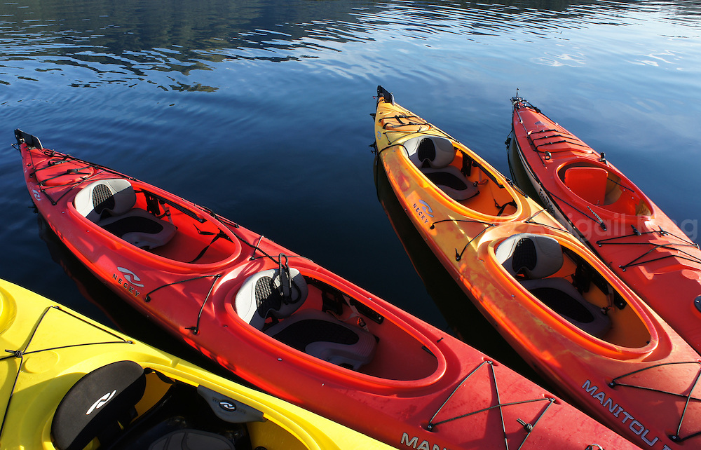 Photos from a kayak expedition to southeast Alaska. Featuring red and yellow kayaks against clear blue water, mountains and cloud-streaked skies.