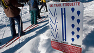 Three adults ski past a cross country ski trail etiquette sign in Bend, Oregon.