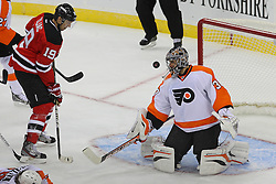 Jan 22, 2013; Newark, NJ, USA; Philadelphia Flyers goalie Ilya Bryzgalov (30) makes a save while New Jersey Devils center Travis Zajac (19) looks for the rebound during the second period at the Prudential Center.