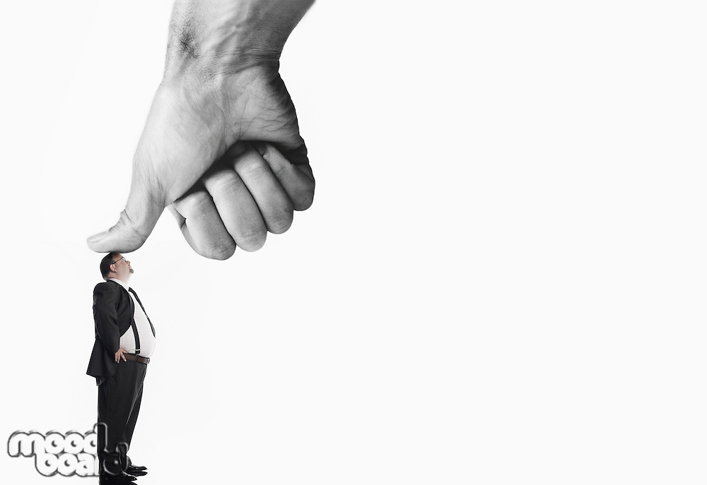 Businessman being pressed by thumb of giant hand, digital composite, colour enhanced, side view