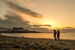 © Licensed to London News Pictures. 31/12/2016. Aberystwyth, Wales, UK. People walking  on the beach as the sun sets over the sea in Aberystwyth on the west Wales coast on the last day of the year - - the weather in the west has been clear, in sharp contrast to the thick fog covering much of south east England. Photo credit: Keith Morris/LNP
