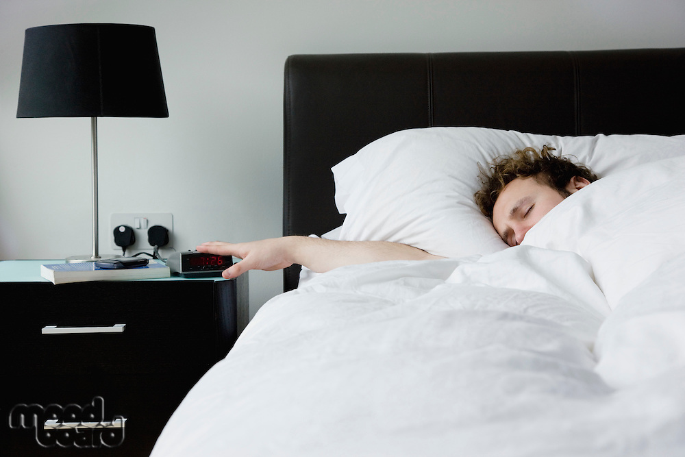 Man holding hand on alarm clock lying in bed