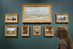 "© Licensed to London News Pictures. 04/08/2020. LONDON, UK. A staff member poses with works by Delacroix and Corot in a recreation of a display at Ordrupgaard. Preview of ""Gauguin and the Impressionists : Masterpieces from the Ordrupgaard Collection"" at the Royal Academy of Arts in Piccadilly.  60 works from a collection of Impressionist paintings, assembled by wealthy Danish couple Wilhelm and Henny Hansen, are on show 7 August to 18 October 2020, and includes masterpieces by Gauguin, Degas, Monet, Morisot, Pissarro, Renoir and Sisley.  Photo credit: Stephen Chung/LNP"