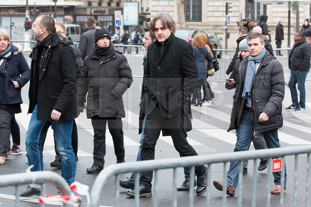 """© Licensed to London News Pictures. 10/01/2016. France, Paris. Charlie Hebdo Editor Laurent Sourisseau """"Riss"""" leaves after the anniversary ceremony on Place de le Republique surrounded by his 24/7 police protection. Today January 10th 2016. Photo credit: Hugo Michiels/LNP"""