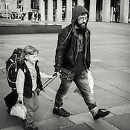Father and daughter packt with traveling gear walking in central Bergen Norway