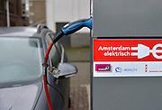 Nederland, Amsterdam, 17-12-2014De eigenaar van een elektrisch aangedreven auto laadt zijn voertuig op bij een laadpaal van Essent, gemeente, mobility,FOTO: FLIP FRANSSEN/ HOLLANDSE HOOGTE