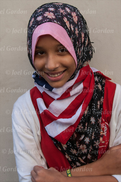 Portrait of smiling American Muslim  teenage girl wearing American Flag scarf.<br /> <br /> She is one of the many faces of people showing her ethnic pride who were marching in the 2014 Muslim Day Parade in New York.<br /> <br /> She is wearing the tradition headdress / headdress scarf call a Hijab.